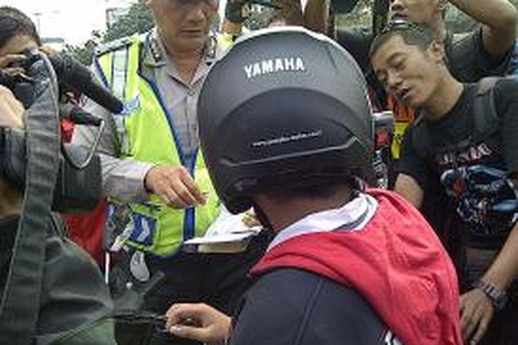 Polisi menilang salah satu pelajar di bilangan Pramuka, Jakarta Timur, Selasa (10/9/2013). Dari razia tersebut, polisi menilang 35 pelajar yang mengemudi tanpa SIM.