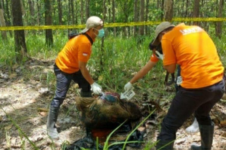 Polisi mengevakuasimayat perempuan terbungkus kantong plastik hitam di kawasan hutan wilayah Dusun Besole, Desa Juworo, Kecamatan Geyer, Kabupaten Grobogan, Jawa Tengah, Rabu (13/10/2021).