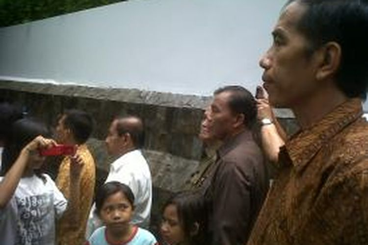 Gubernur DKI Jakarta Joko Widodo saat memperhatikan pidato Presiden SBY di kantor Baznas, Kebon Sirih, Jakarta, Senin (5/8/2013). Jokowi tampak serius memperhatikan pidato SBY, padahal di depannya ada seorang anak kecil yang mengarahkan kamera telepon genggamnya ke arah Jokowi.