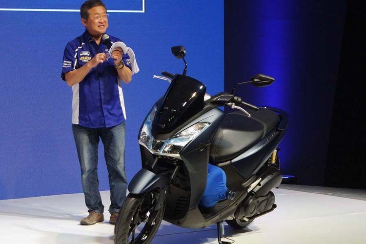 Presiden Direktur Yamaha Indonesia Motor Manufacturing Minoru Morimoto mempraktekan ruang kaki Yamaha Lexi 125 muat botol galon minuman.