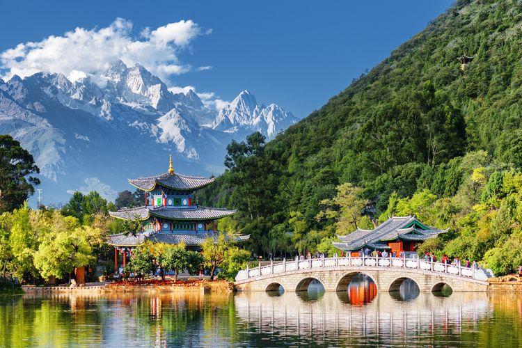 Panorama menakjubkan Jade Dragon Snow Mountain dan the Black Dragon Pool, di Lijiang, Provinsi Yunnan, China. Nampak juga Suocui Bridge di atas kolam di Jade Spring Park.