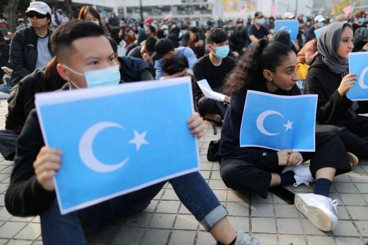 Para demonstran di Hong Kong membawa bendera Turkistan timur dalam aksi untuk membela HAM warga etnis Uighur di Xinjiang, China.