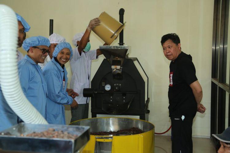 Menteri BUMN Rini Soemarno (seragam biru) didampingi Bupati Banyuwangi Abdullah Azwar Anas saat meninjau langsung proses pengolahan cokelat di Pabrik Pengolahan Cokelat di Glenmore, Banyuwangi, Jawa Timur, Sabtu (16/2/2019).