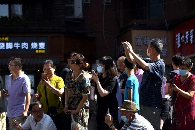 Orang-orang berdiri di jalan yang mengarah ke Konsulat AS di Chengdu, provinsi Sichuan di China barat daya pada 27 Juli 2020. Bendera Amerika diturunkan di konsulat Amerika Serikat di Chengdu, beberapa hari setelah Beijing memerintahkannya untuk menutup sebagai pembalasan atas penutupan pabrik tersebut. Konsulat Tiongkok di Houston.