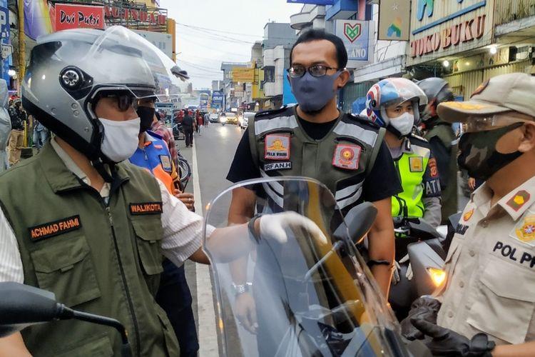 Wali Kota Sukabumi Achmad Fahmi (kiri) mengendarai sepeda motor saat berbincang dengan aparatnya dalam perjalanan pengecekan ke sejumlah wilayah di Jalan Ahmad Yani, Minggu (3/5/2020), jelang penerapan PSBB Jabar yang dimulai 6 Mei 2020.