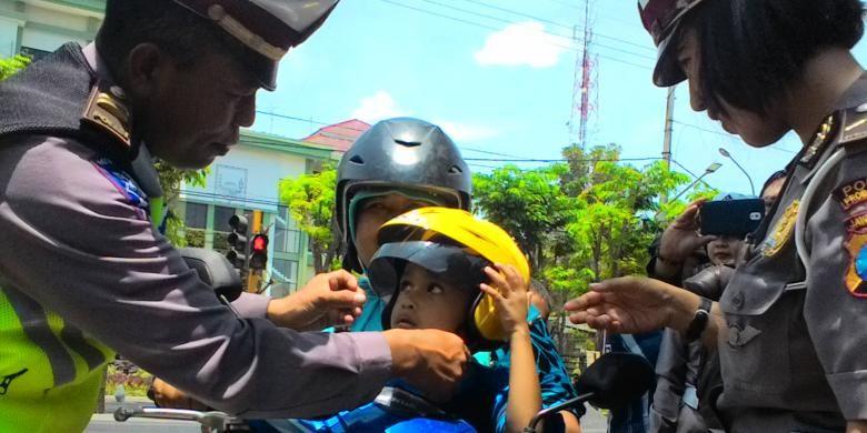 Seorang anak mendapatkan helm gratis dari Polisi dalam operasi simpatik di Kabupaten Probolinggo.
