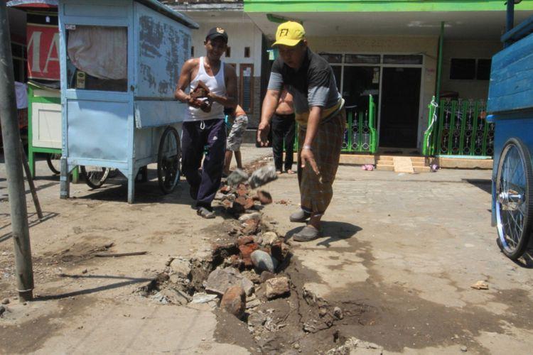 Warga Kelurahan Mangunharjo sukarela menutup galian jaringan gas yang amblas karena hujan. Galian tersebut amblas karena tanah penutup galian kurang padat, Kamis (29/11/2018).