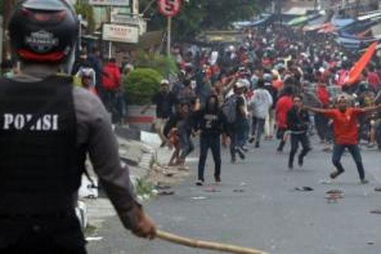 Petugas mencoba menghalau ratusan pendukung Persija Jakarta (Jakmania) yang akan mencoba masuk ke area Gelora Bung Karno di Kawasan Palmerah, Jakarta Pusat, Minggu (18/10/2015).