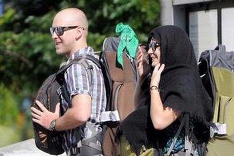 Turis mengenakan kerudung ketika melintas di depan Masjid Raya Baiturrahman, Banda Aceh, Rabu (13/2/2013). Pemberlakuan syariat Islam di Aceh menjadi salah satu daya tarik bagi turis asing.