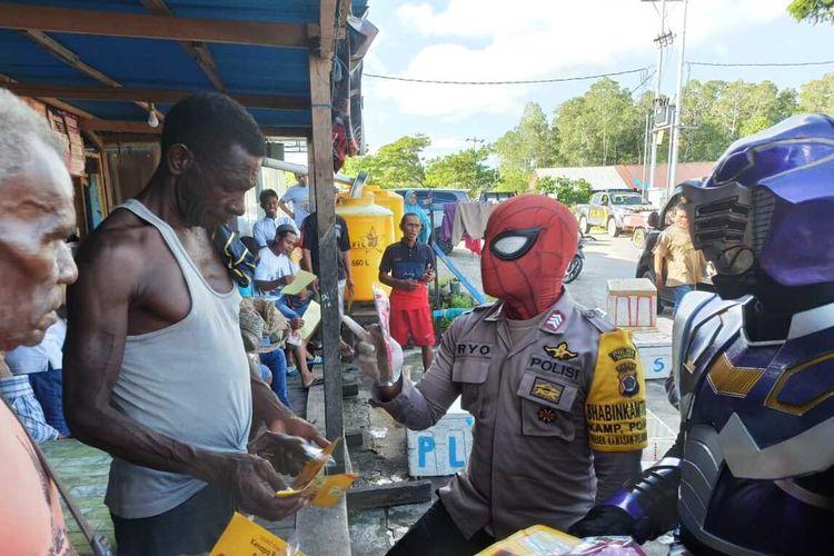 Anggota kepolisian dengan menggunakan kostum super hero saat memberikan sosialisasi Covid-19 kepada warga di Distrik Mimika Timur, Mimika, Papua, Minggu (26/4/2020).