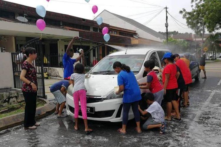 Anak-anak dan remaja di Malaysia membuka usaha cuci mobil di lingkungan perumahan, di Kuala Lumpur, Sabtu (2/6/2018). Mereka ingin mendonasikan uang yang terkumpul untuk membayar utang negara. (Facebook/Teresa Kok)