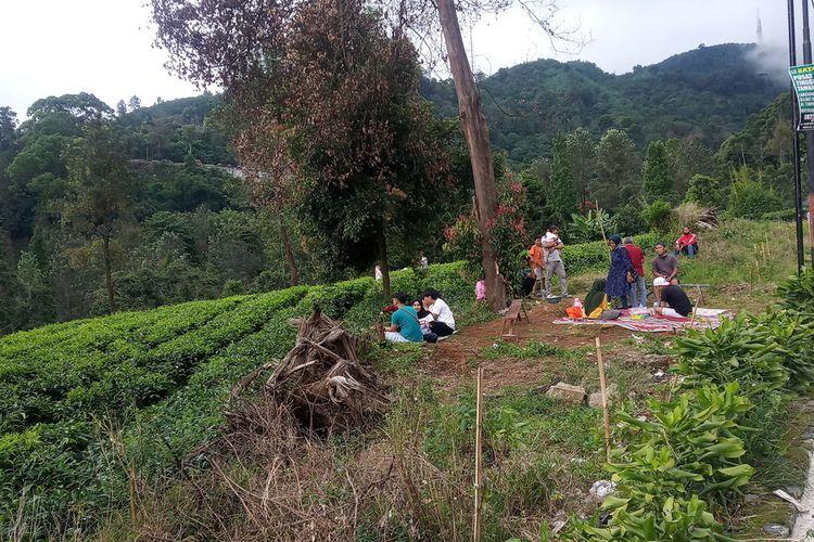 Wisatawan dari berbagai daerah nampak duduk menggunakan tikar sambil menikmati pemandangan kebun teh di Puncak Bogor, Jawa Barat, Senin (25/5/2020).