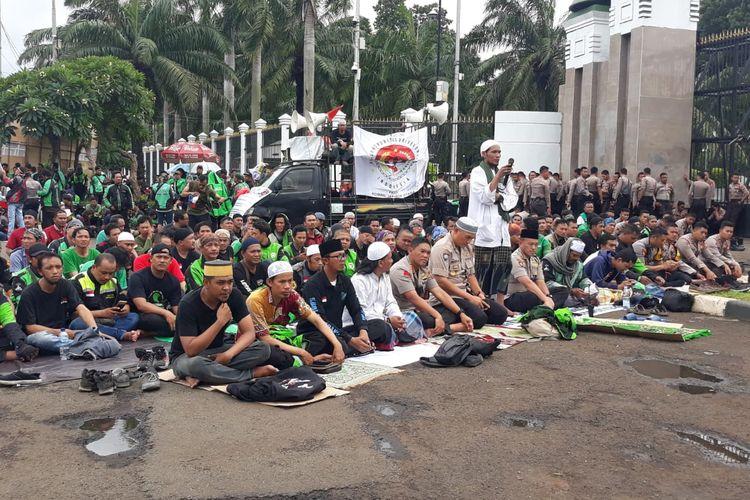 Sebagian massa aksi pengemudi ojek online (ojol) melaksanakan ibadah salat Jumat di depan gedung DPR/MPR, Senayan, Jakarta, Jumat (28/2/2020).