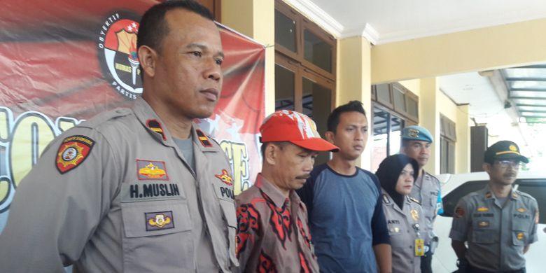 Guru PNS AS (bertopi) sebelum memberikan keterangan pers di Mapolres Garut, Selasa (21/5/2019). AS dotangkap karena menyebarkan pesan pengeboman massal di Jakarta via WhatsApp.