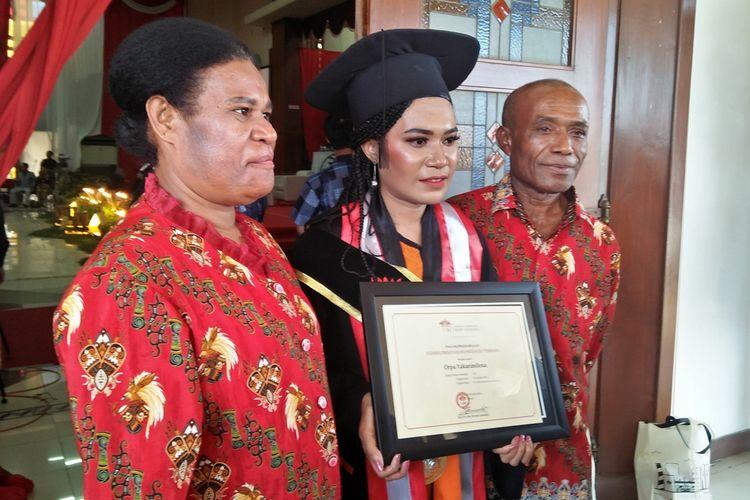 Orpa Yakarimilena (tengah) bersama kedua orang tuanya, usai diwisuda sebagai salah seorang lulusan terbaik UISI.