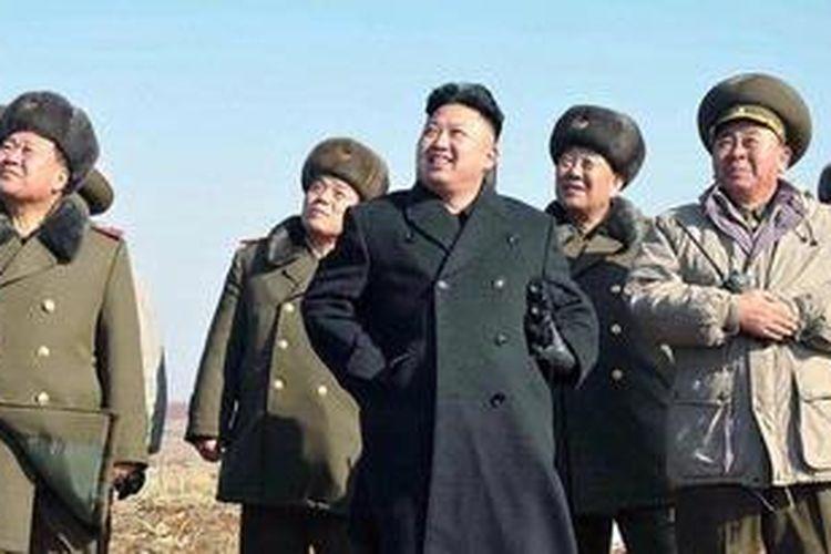 Pemimpin Korea Utara Kim Jong Un bersama sejumlah petinggi militer menyaksikan latihan pasukan payung Angkatan Udara Korea Utara pada 23 Februari 2013.