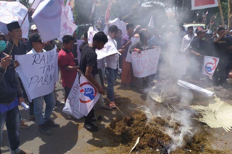 Petani tembakau di Pamekasan berunjuk rasa di depan kantor Bupati Pamekasan sambil membakar tembakau rajangan yang baru selesai dipanen.