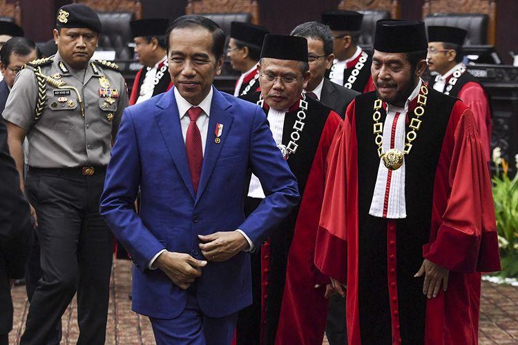 Presiden Joko Widodo (kiri) bersama Ketua Mahkamah Konstitusi (MK) Anwar Usman (kanan) dan Wakil Ketua MK Aswanto (tengah) meninggalkan ruang sidang seusai mengikuti sidang pleno penyampaian laporan tahun 2019 di Gedung MK, Jakarta, Selasa (28/1/2020). Sejak berdiri pada tahun 2003 hingga Desember 2019 MK telah menerima sebanyak 3.005 perkara.