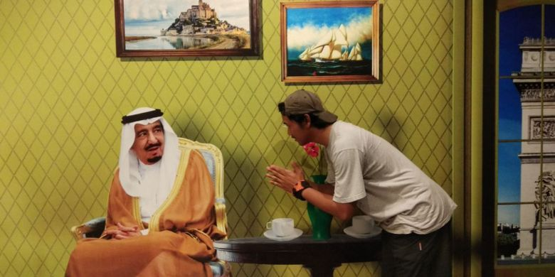 Pose Raja Salman terlihat sedang duduk termenung di kursi dengan dua buah gelas serta vas bunga terletak di atas meja. Ia seakan-akan memunculkan mimik muka terkejut melihat pengunjung yang datang.