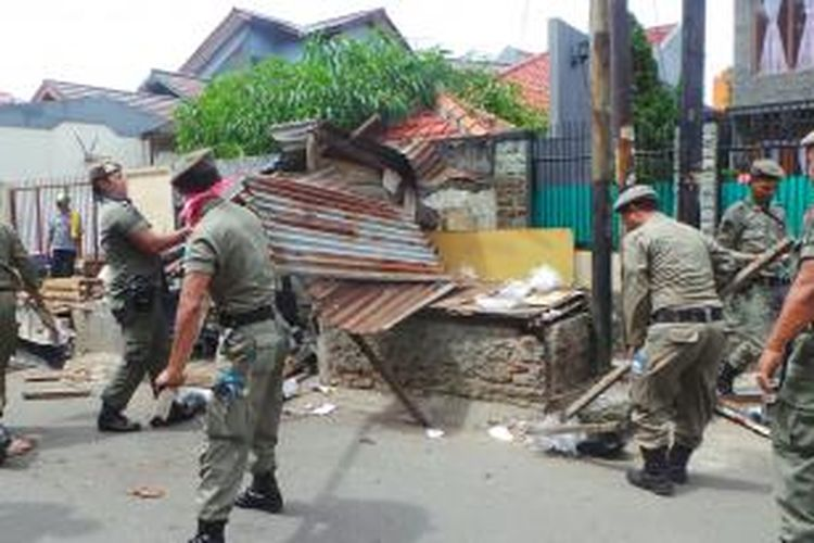 Lapak pasar kaget di pemukiman warga di Jalan Metro Jaya, Kayu Putih, Jakarta Timur dibongkar petugas. Jumat (24/4/2015).