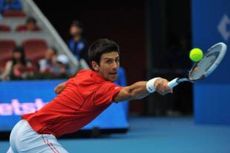 Petenis Serbia, Novak Djokovic, berusaha  menjangkau bola Fernando Verdasco dari Spanyol, saat berhadapan di babak kedua China Open, yang berlangsung di China, Kamis (3/10/2013).