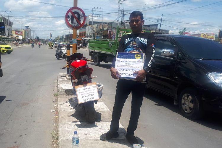Muhammad Hasyriadi Syam tengah menggalang dana dan memajang motornya yang dijual untuk membantu korban bencana banjir bandang Jayapura, Rabu (20/3/2019)