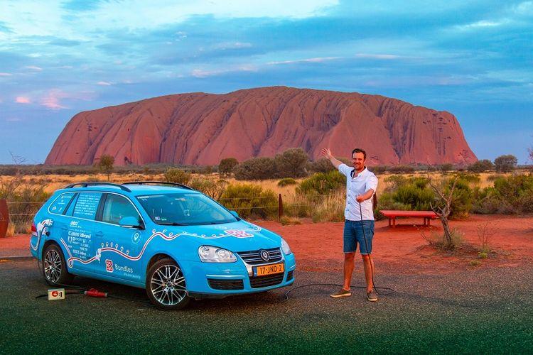 Dalam foto yang diambil pada 31 Desember 2018 memperlihatkan, warga Belanda Wiebe Wakker berpose di Uluru, Northern Territory, Australia dengan mobil listrik miliknya The Blue Bandit dalam perjalanan keliling dunianya.