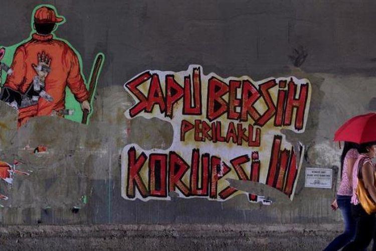 Warga melintas di depan poster berisi kritikan terhadap perilaku korupsi di kolong jalan kereta api Manggarai, Jakarta Selatan, Minggu (16/12/2012). Kritikan terhadap pelaku koruptor terus disuarakan oleh aktivis untuk mendorong tindakan lebih tegas dalam pemberantasan korupsi dan penegakan hukum lainnya.