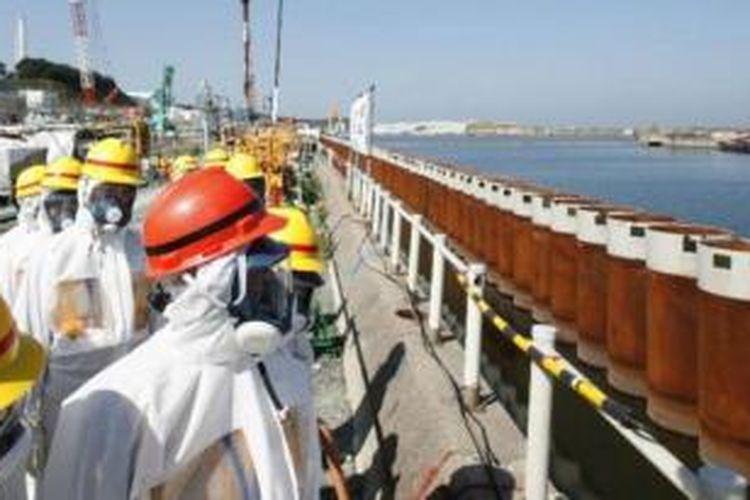 Foto ini diambil pada 19 September 2013. PM Jepang Shinzo Abe sedang meninjau tembok yang berasal dari pipa baja dibangun di sepanjang pesisir dekat dengan PLTN Fukushima yang rusak karena diterjang tsunami dan gempa pada 2011.