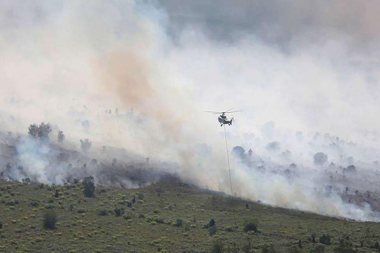 Sebuah helikopter Super Puma AS332L1 milik Asia Pulp & Paper (APP) Sinar Mas Forestry bersiap melakukan pengeboman air (water bombing) terhadap hutan dan lahan perkebunan sawit rakyat yang terbakar di Desa Gurun Panjang di Dumai, Dumai, Riau, Senin (25/2/2019). APP Sinar Mas Forestry mengerahkan dua unit helikopter Super Puma AS332L1 dan AS332c PK-DAN milik perusahaan itu untuk membantu memadamkan api kebakaran hutan dan lahan perkebunan sawit milik rakyat akibat cuaca panas di Desa Bukit Kerikil Bengkalis dan Desa Gurun Panjang Dumai dengan cara pengeboman air lewat udara.