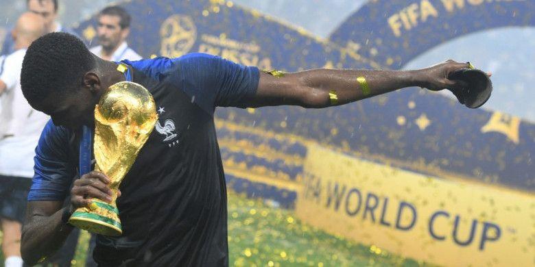 Gaya Paul Pogba saat memegang trofi Piala Dunia 2018 yang dimenanginya bersama timnas Prancis seusai mengalahkan Kroasia pada final yang berlangsung di Stadion Luzhniki pada 15 Juli 2018.