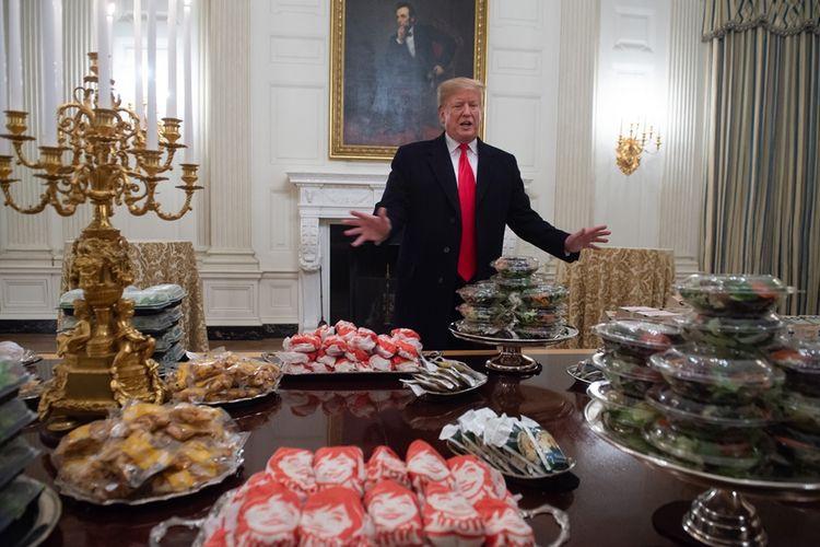 Presiden AS Donald Trump menunjukkan meja makan penuh dengan makanan cepat saji ala Amerika, yang akan disajikan untuk tim juara liga football nasional, Clemson Tigers, di ruang makan Gedung Putih, Senin (14/1/2019) malam.