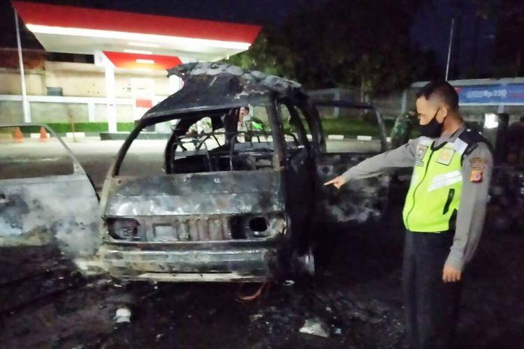 Seorang anggota polisi memerlihatkan kondisi mobil pikap pengangkut tabung gas elpiji 3 kg yang hangus terbakar di area sebuah SPBU di Warungkondang, Cianjur, Jawa Barat, Kamis (22/10/2020) malam.