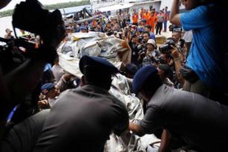 Anggota Kapal Polisi Punai, menurunkan serpihan dari pesawat AirAsia QZ8501di Pelabuhan Kumai, Kalimantan Tengah, Kamis (1/1/2015). Serpihan ini ditemukan oleh kapal Malaysia yang turut serta dalam pencarian dan kemudian dipindahkan ke kapal polisi.