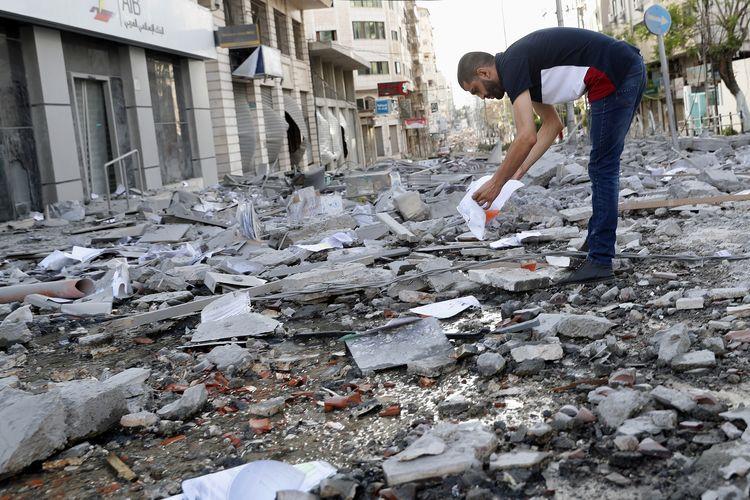 Seorang pria mengais puing-puing gedung klinik perawatan kesehatan Gaza, yang hancur diserang Israel dari udara pada Senin (17/5/2021).