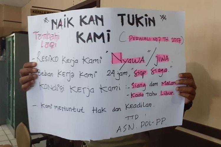 Poster yang dibawa salah satu anggota Satpol PP saat menggelar unjuk rasa di kantor BKD Banjarmasin menuntut kenaikan Tukin. Dalam aksinya itu, anggota satpol PP mengamuk dan merusak sejumlah fasilitas di ruang BKD, Selasa (18/2/2020).