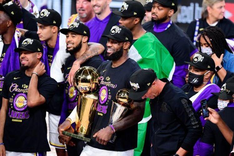 LeBron James (tengah) membawa trofi juara NBA dan pemain terbaik Final NBA seusai mengantar LA Lakers mengalahkan Miami Heat pada Gim 6 Final yang berlangsung di AdventHealth Arena, Orlando, Amerika Serikat, Senin (12/10/2020) pagi WIB.