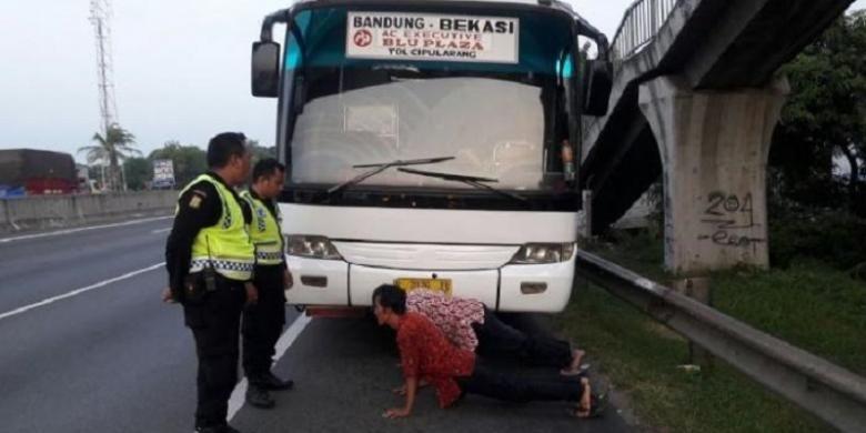 Petugas Keamanan dan Ketertiban PT Jasa Marga cabang Jakarta-Cikampek meminta sopir dan kernet bus Primajasa untuk push up di badan jalan KM 57 yang mengarah ke Jakarta.