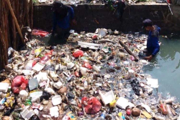 Petugas Satgas dari Pemerintah Kota depok mengangkat bendungan sampah di Setu Pedongkelan, Selasa (27/11/2018).