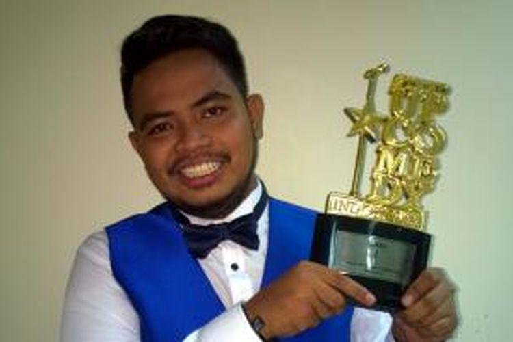 Komika asal Bima, NTB, Rigen, berpose mengangkat piala setelah berhasil menjadi juara 1 kompetisi Stand Up Comedy Indonesia Season 5 (SUCI 5) yang ditayangkan Kompas TV. Rigen berhasil menjadi juara setelah menyisihkan Rahmet dan Indra di babak Grand Final SUCI 5 di Balai Kartini, Jakarta, Jumat (3/7/2015).