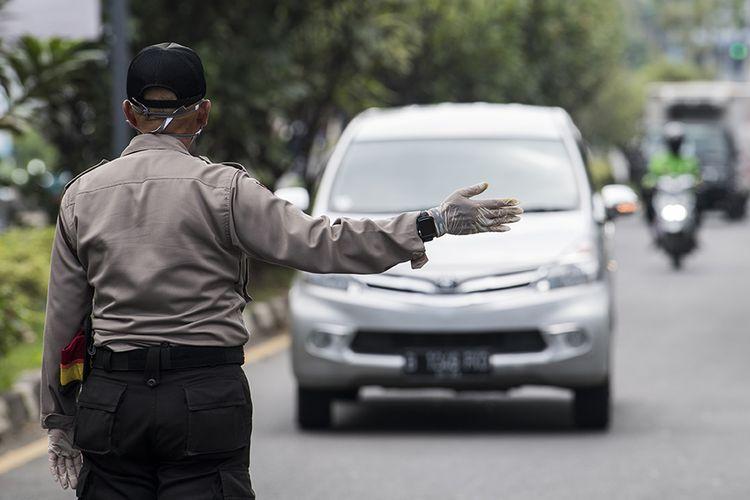 Polisi mengarahkan kendaraan roda empat untuk menjalani pemeriksaan saat penerapan pembatasan sosial berskala besar (PSBB) di Pasteur, Bandung, Jawa Barat, Rabu (22/4/2020). Pemeriksaan tersebut dilakukan untuk mengingatkan masyarakat agar menerapkan PSBB selama 14 hari dalam rangka percepatan penanganan Covid-19.