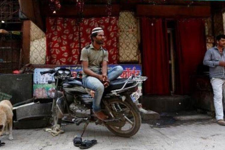 Sejumla warga duduk-duduk di depan sebuah restoran yang ditutup di pasar Gurugram, Haryana, India.