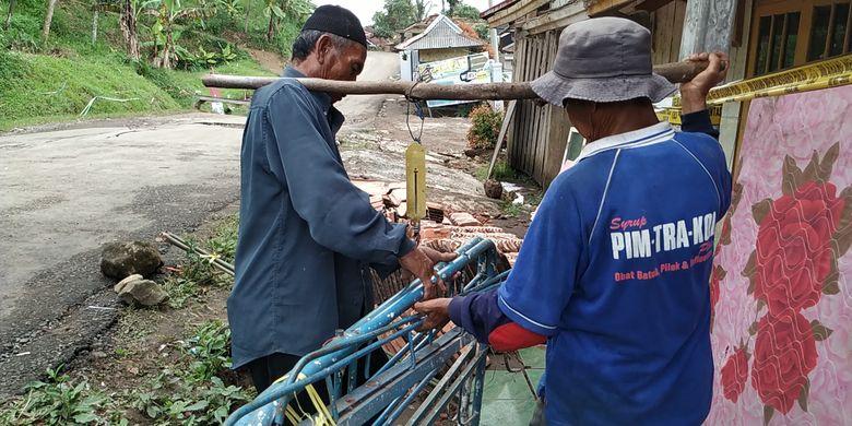 Uma (kiri) warga terdampak bencana gerakan tanah menimbang tempat tidur besi di Kampung Gunubhbatu, Desa Kertaangsana, Nyalindung, Sukabumi, Jawa Barat, Rabu (1/5/2019).
