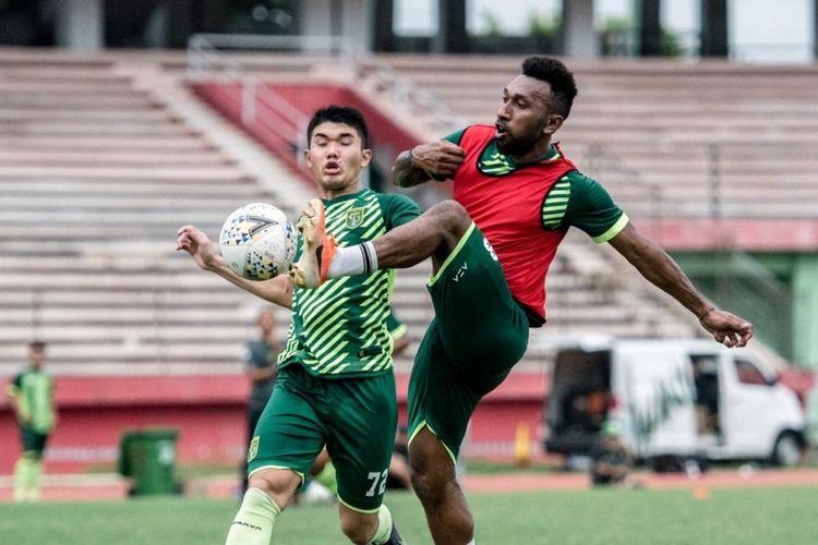 Penyerang anyar Persebaya Patrich Steve Wanggai (kanan) berebut bola dengan Rifky Afryan Hartono, pemain Persebaya U-20, pada sesi latihan di Stadion Gelora Delta Sidoarjo sore tadi. Patrich langsung mengikuti latihan meski baru diperkenalkan siang tadi. (Persebaya)