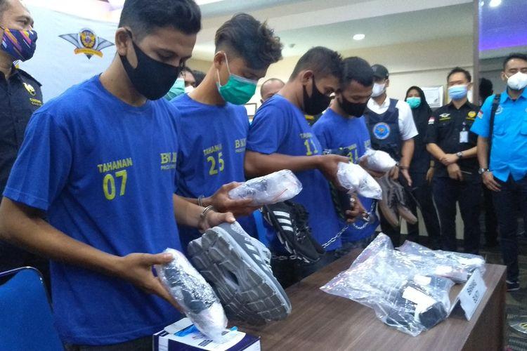 Empat orang tersangka menunjukkan sepatu yang digunakannya untuk menyembunyikan 2 kg sabu saat akan terbang ke Solo. Mereka ditangkap di Bandara Internasional Kualanamu pada Jumat (22/1/2021) sore.