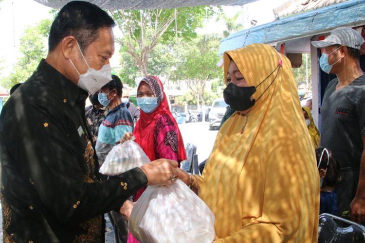 Bupati Lamongan Yuhronur Efendi (kiri) saat memberikan bantuan kepada para pedagang di kompleks makam Sunan Drajat, Jumat (6/8/2021).
