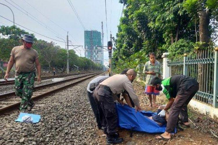 Petugas mengevakuasi jenazah pria yang tewas tertabrak kereta di kawasan Tanjung Barat, Jakarta Selatan, Jumat (22/5/2020)