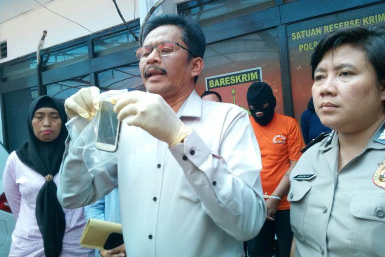 Wakasatreskrim Polrestabes Bandung Kompol Suparma tengah memperlihatkan barang bukti ponsel berisi chat tersangka yang mengancam korban. Tersangka DN tega cabuli anak kandungnya hingga hamil.
