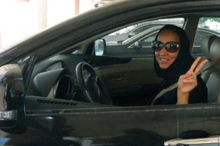 Aktivis perempuan Arab Saudi Manal al-Sharif, yang kini tinggal di Uni Emirat Arab, menunjukkan lambang kemenangan dengan jarinya saat dia mengemudikan mobilnya di Dubai.