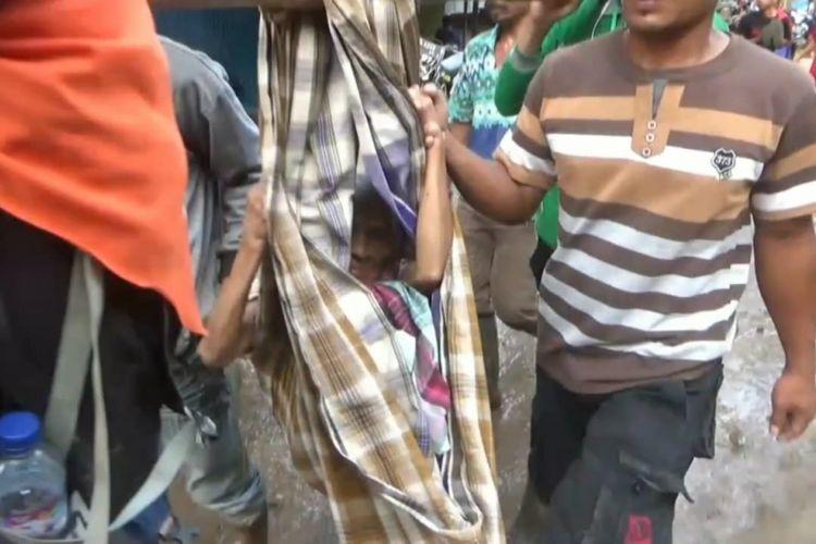 Nenek Hartati (64) tengah dievakuasi menggunakan sarung dan bambu oleh relawan lantaran kondisinya yang lemas akibat kelaparan selama berhari hari dalam bencana longsor yang melanda Kabupaten Gowa, Sulawesi Selatan, Senin (28/1/2019).